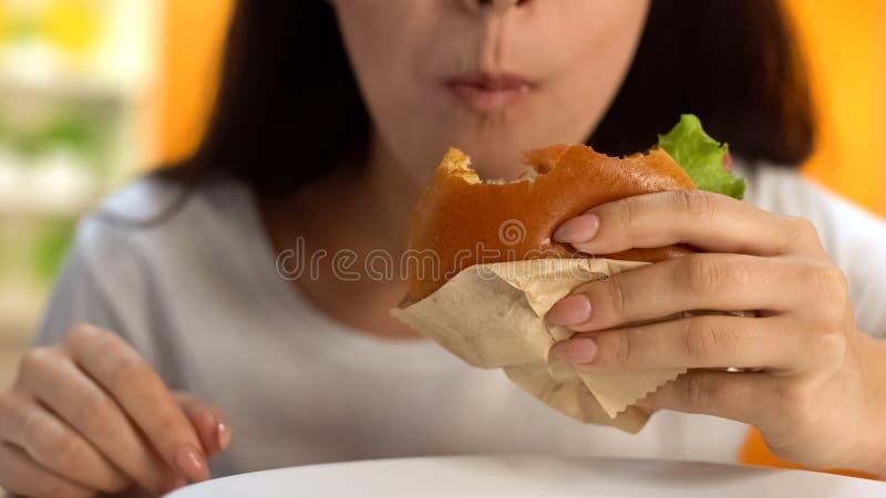 Пристрастившийся к женщине фаст-фуда жуя крупный план бургера, нездоровый аппетит питания стоковое фото rf