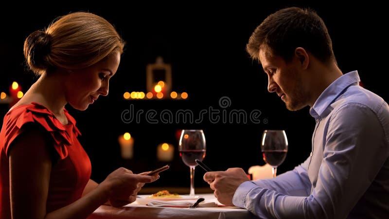 Пристрастившийся пары используя смартфоны, игнорируя один другого на романтичном обедающем стоковые изображения