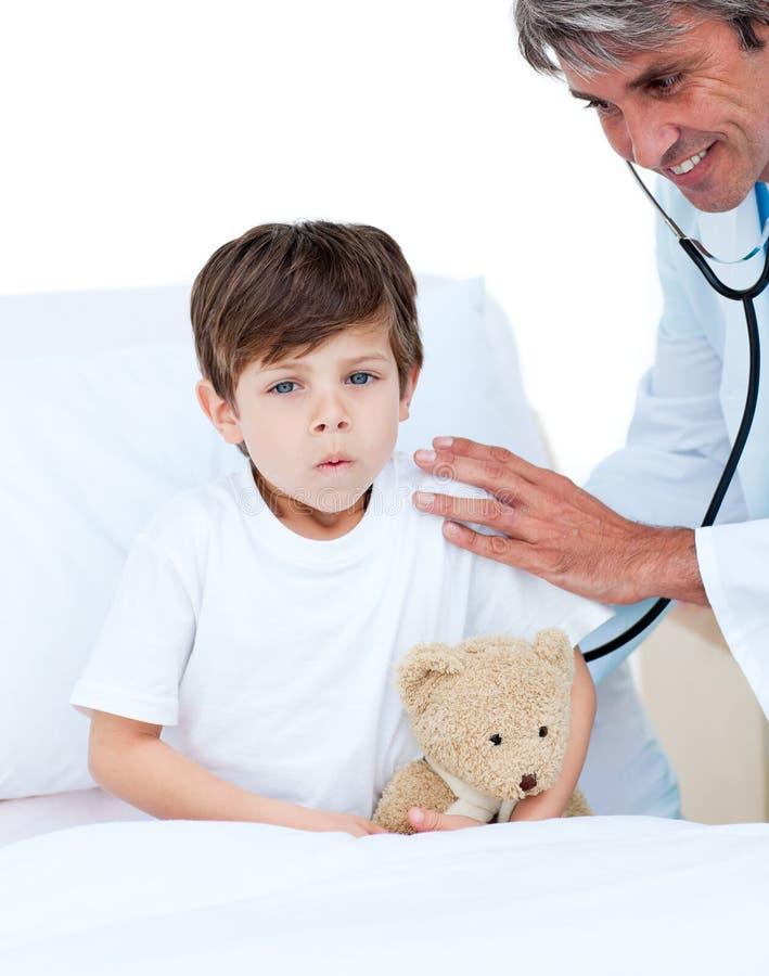 присутствовать на поднимающем вверх проверки мальчика милое немного медицинское стоковое изображение