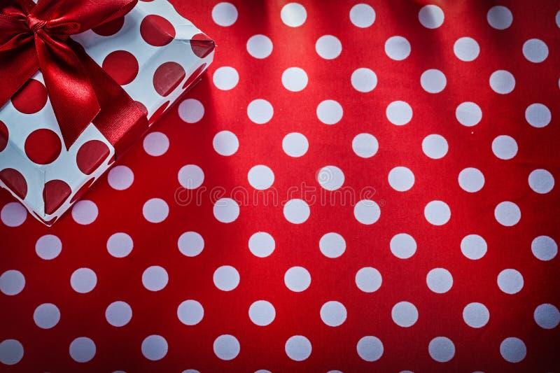Присутствующая коробка с связанной лентой на празднике скатерти полька-точки красном стоковые фотографии rf