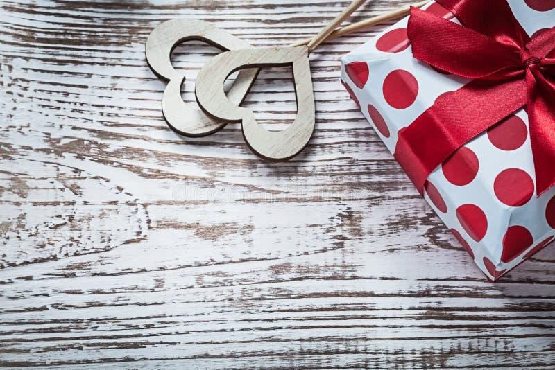Присутствующая коробка с связанными красными сердцами древесины смычка на винтажном деревянном хряке стоковое изображение