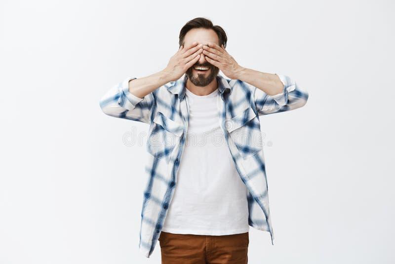 Присягните что я не делает взгляд украдкой Очаровательный шаловливый и смешной зрелый отец в проверенной рубашке, покрывающ глаза стоковое изображение rf