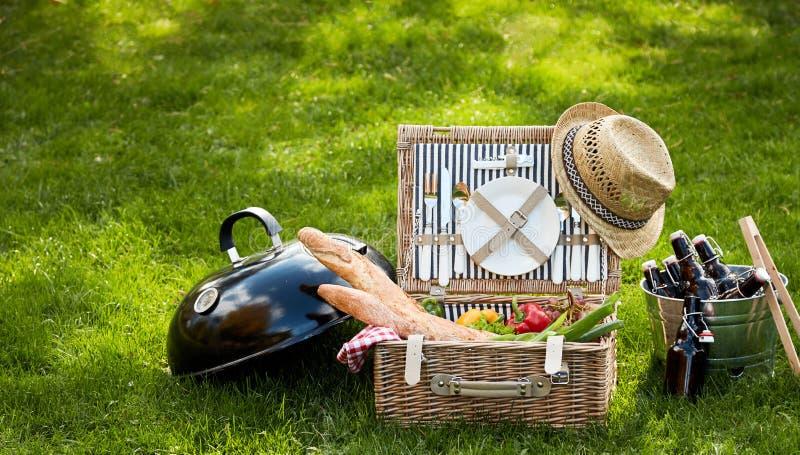 Прифронтовой взгляд корзины пикника сидя в траве стоковые изображения