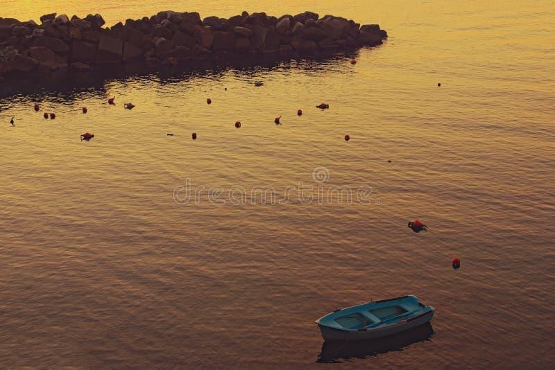 Причаленная голубая рыбацкая лодка в заливе деревни Manarola во время захода солнца Концепция ландшафта и природы Manarola, Cinqu стоковое изображение rf