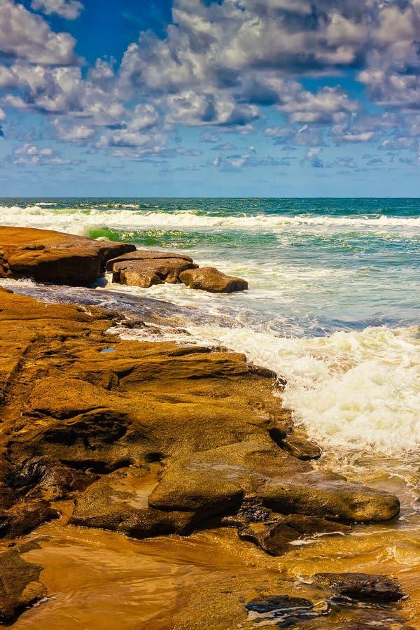 причиненные капельки производят эффект быстрая, котор замерли выдержка затвора утесов брызгая волны воды стоковая фотография rf