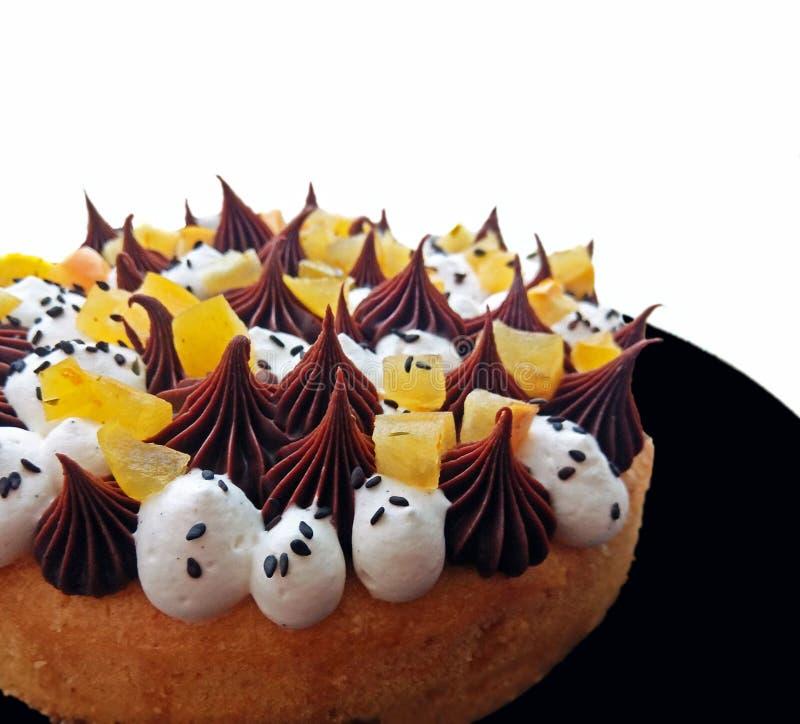 Причудливый влажный оранжевый торт губки с взбитым ganache сливк и шоколада взбрызнутым с семенами сезама стоковые фотографии rf