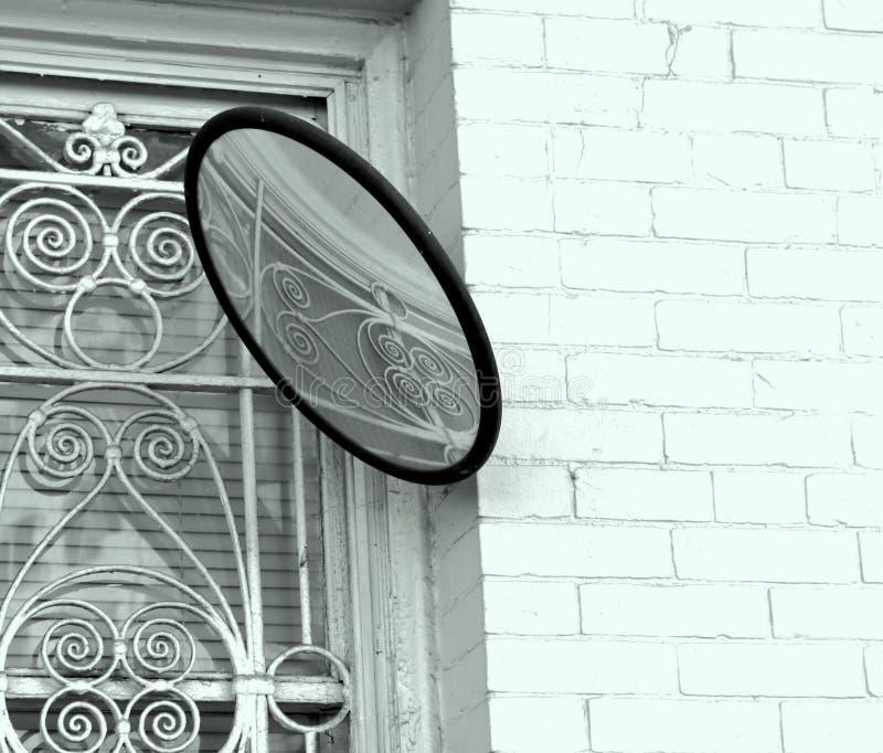 Причудливый Ironwork над окном, белым кирпичом, круглым зеркалом стоковое изображение rf
