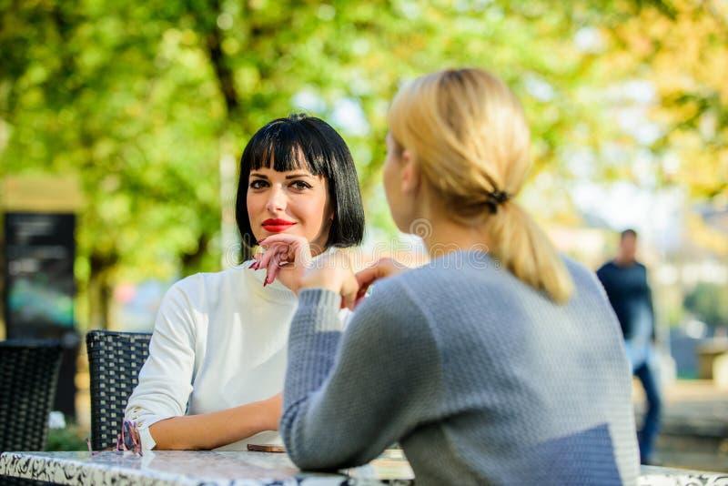 Приятельство или соперничество Подруги выпивают беседу кофе Разговор террасы кафа 2 женщин Приятельство дружелюбное стоковое фото