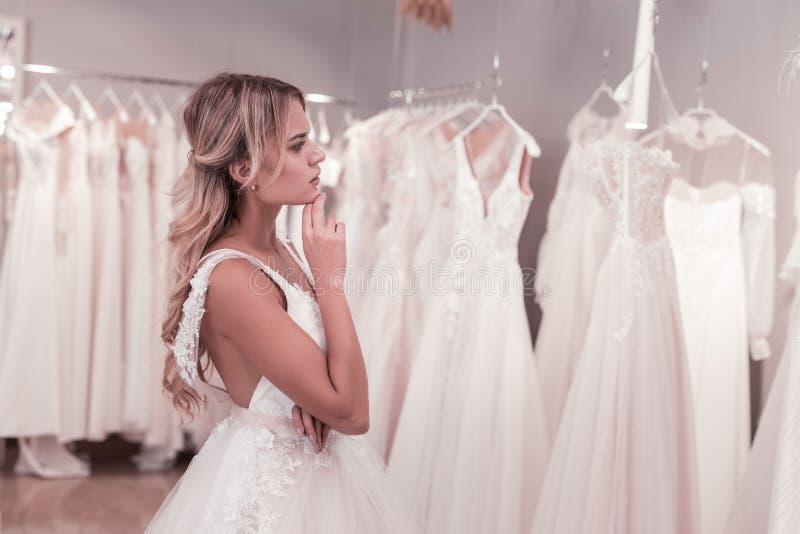 Приятная внимательная невеста смотря платья стоковые фото