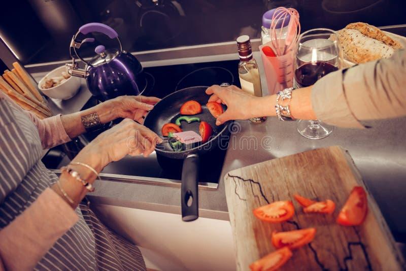 Приятная достигшая возраста женщина кладя томат на сковороду стоковые фотографии rf