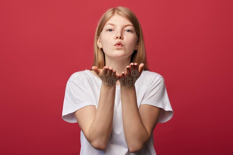 Приятная дружелюбная женщина в белой футболке отправляя поцелуй стоковое изображение rf