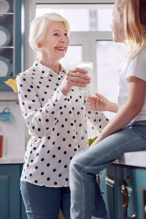 Приятная женщина предлагая ее внучку для того чтобы выпить молоко стоковое изображение