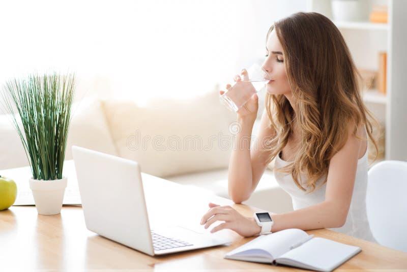 Приятная молодая женщина сидя на таблице стоковое фото