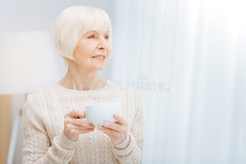 Приятная пожилая женщина держа чашку и смотря в расстояние стоковая фотография