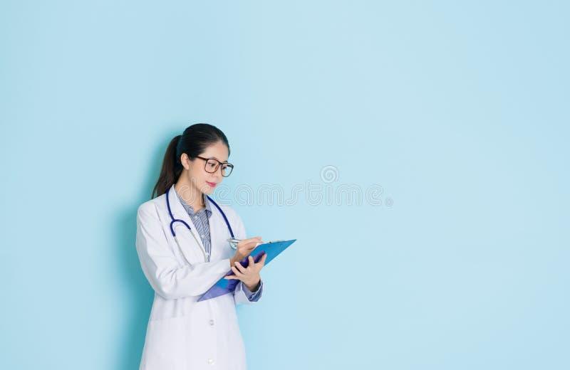Приятно женский доктор клиники держа доску стоковые изображения rf