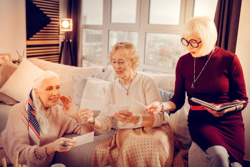 Приятные достигшие возраста женщины смотря фото стоковая фотография rf