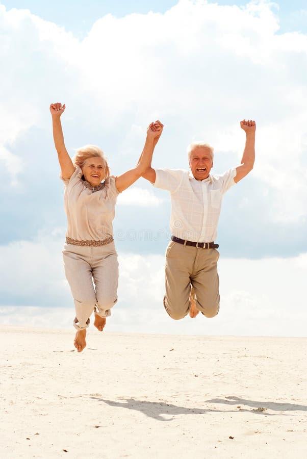 Приятные пожилые пары наслаждаются морским бризом стоковая фотография rf