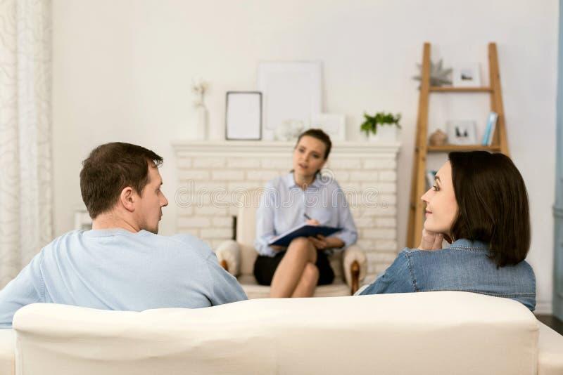 Приятные славные пары сидя на софе стоковое фото rf