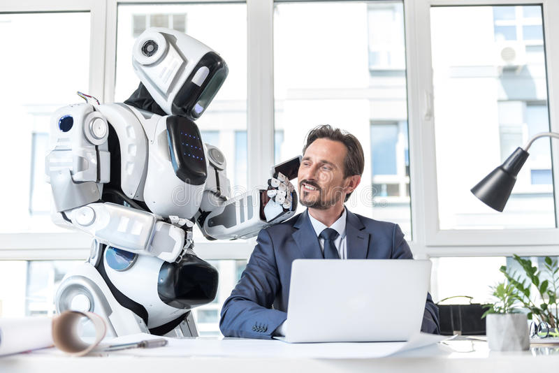 Приятный бизнесмен в костюме и андроид работают с удовольствием стоковые изображения