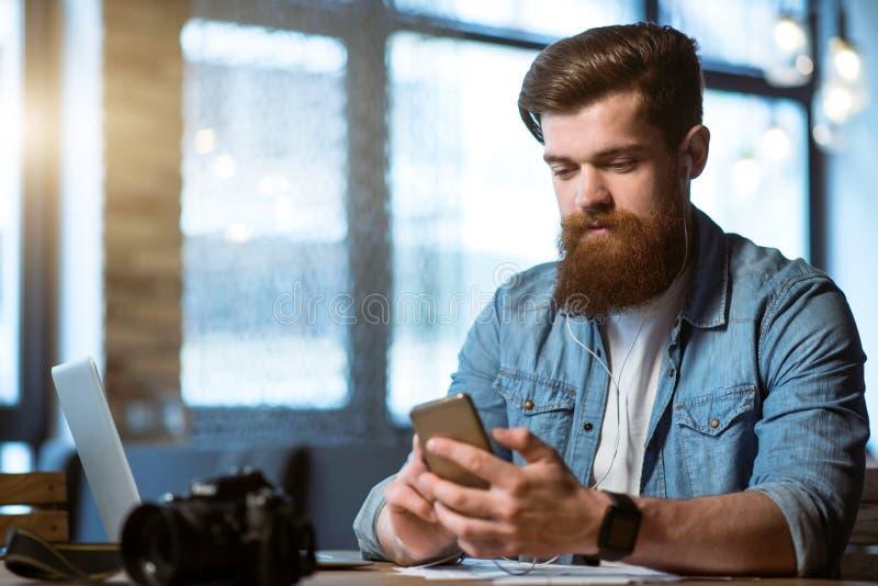 Приятный бородатый человек сидя на таблице стоковое изображение