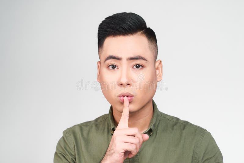 Приятный выглядя восхитительный молодой мужчина держит палец на губах, спрашивает не сказать секретную информацию или не сдержать стоковое изображение rf