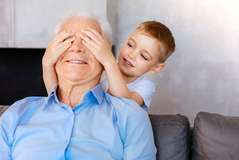 Приятный милый мальчик сидя за его дедом стоковое изображение