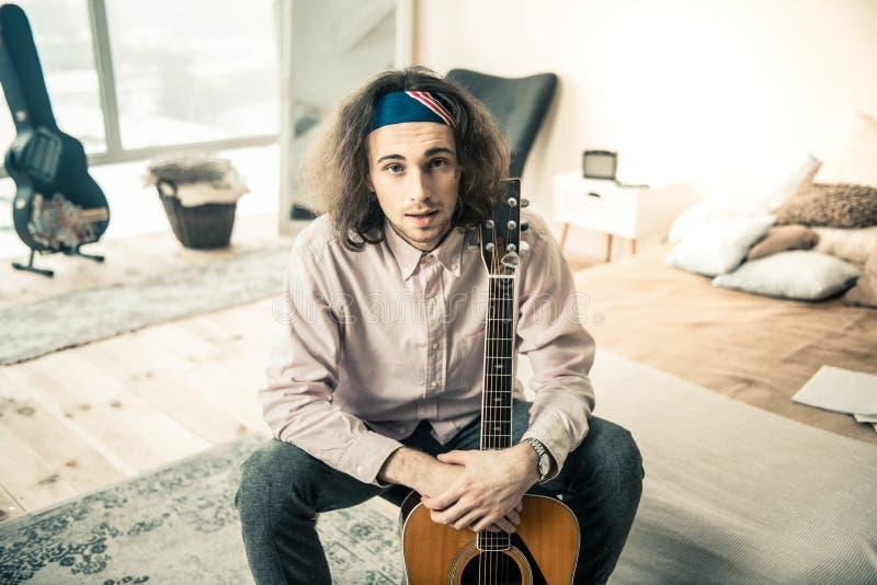 Приятный профессиональный гитарист в светлых рубашке и bandana стоковая фотография