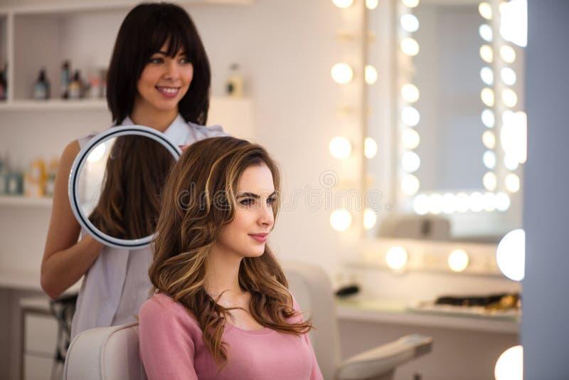 Приятный профессиональный парикмахер работая в салоне стоковое изображение rf