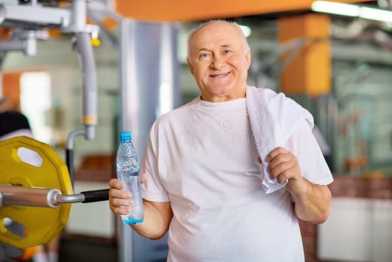 Приятный старший человек держа бутылку воды стоковые фото