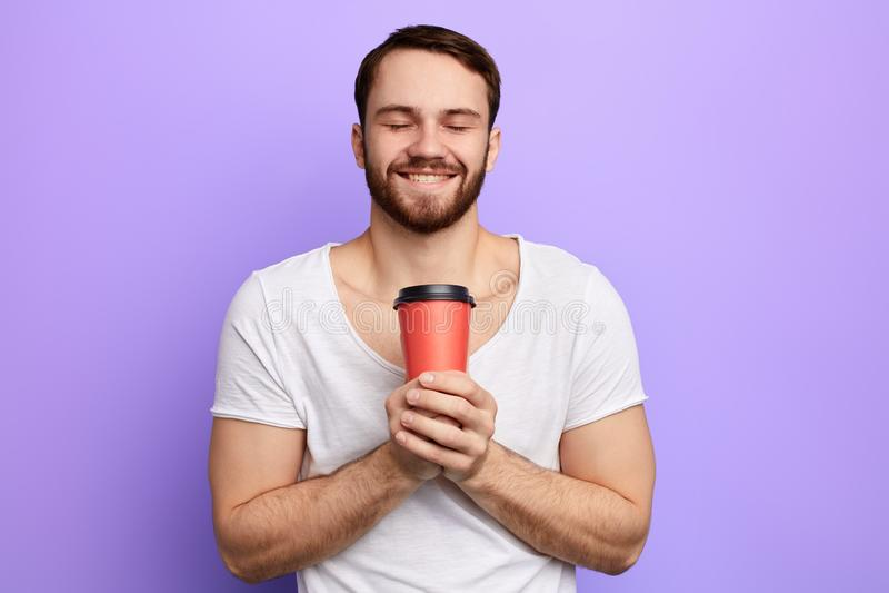 Приятный человек выпивая его любимый кофе стоковые фото