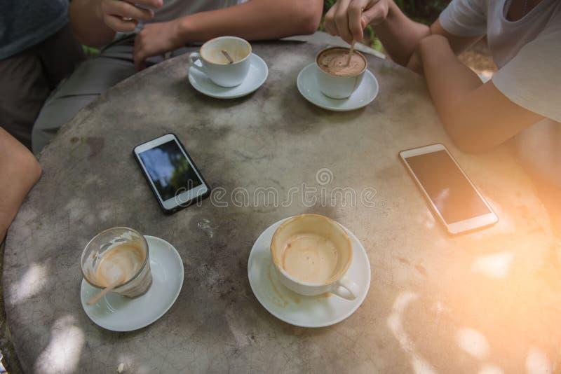 Придайте форму чашки кофе и телефон на таблице в кофейне на утре стоковое фото
