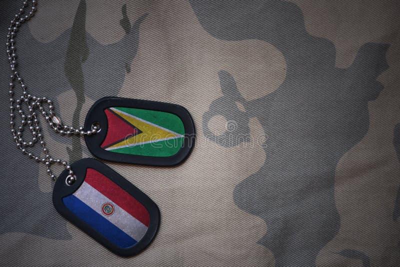 пробел армии, регистрационный номер собаки с флагом Гайаны и Парагвай на хаки предпосылке текстуры стоковая фотография