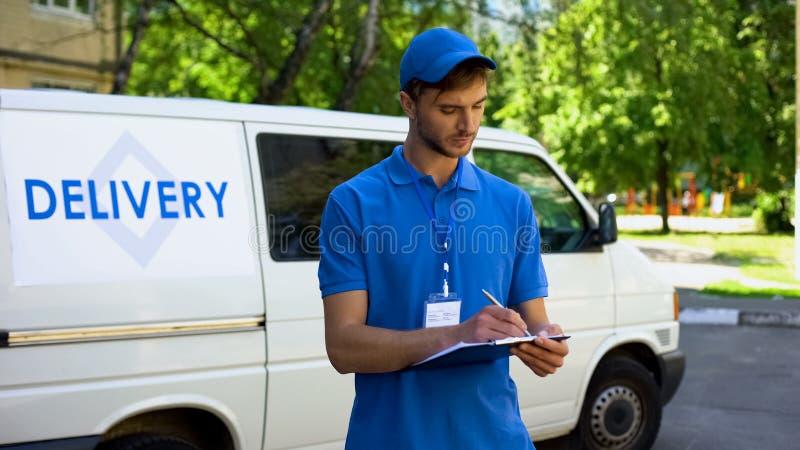Пробел около фургона компании, почтовая служба пакета работника доставляющего покупки на дом заполняя, пересылка стоковые фото