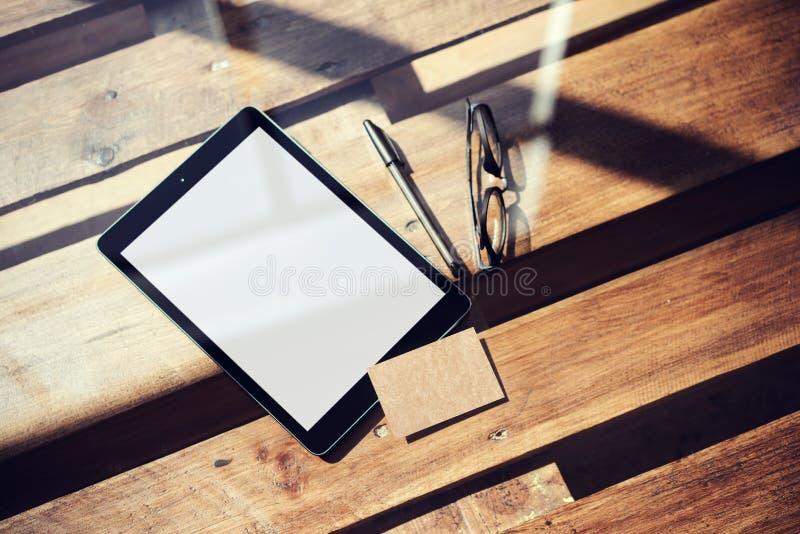 Пробела таблетки крупного плана экран современного белый, таблица стекел деревянная внутри внутренней студии Coworking Пустой диз стоковая фотография