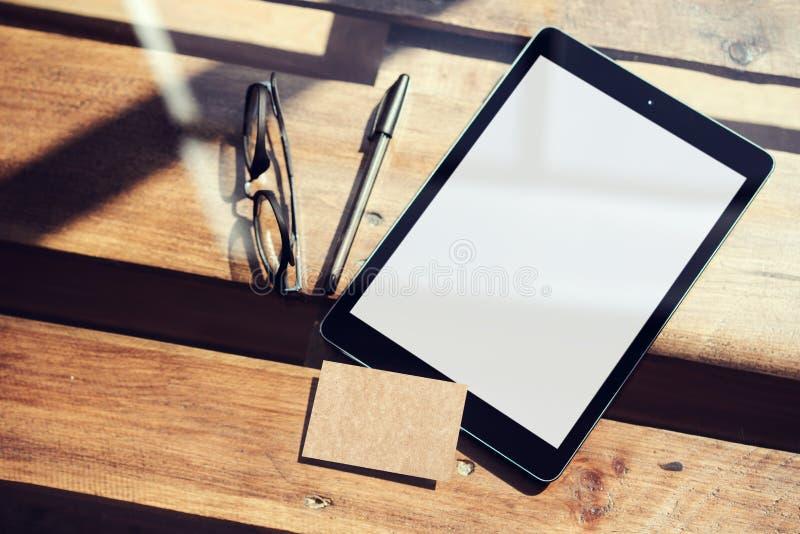 Пробела таблетки крупного плана экран современного белый, таблица стекел деревянная внутри внутреннего Coworking Пустой дисплей,  стоковая фотография rf