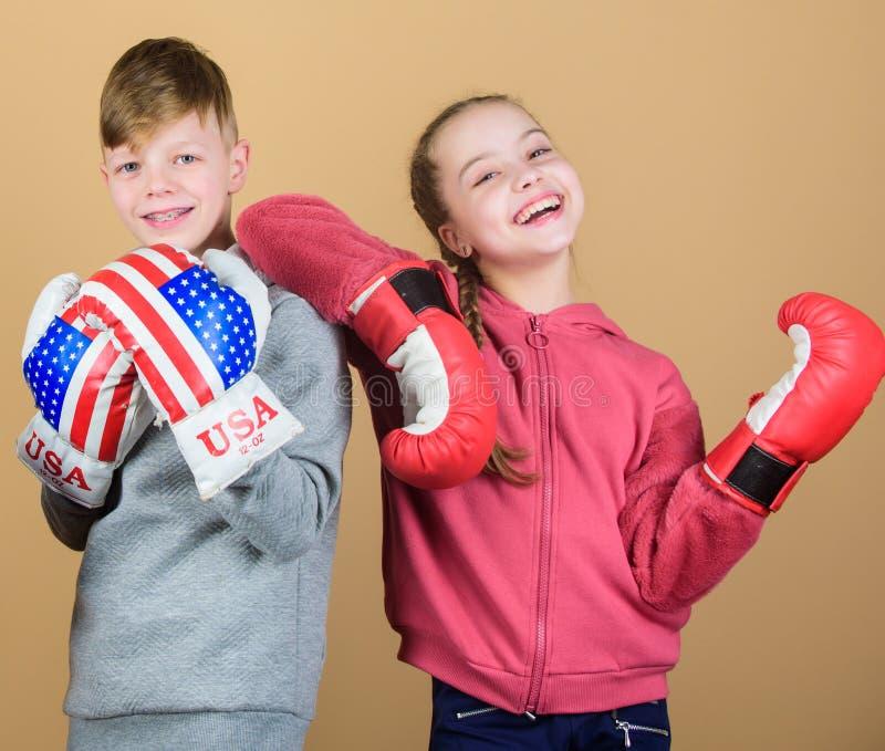 пробивая нокдаун Деятельность при детства Успех спорта Бой приятельства разминка небольшого боксера девушки и мальчика внутри стоковая фотография rf