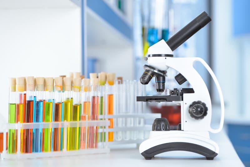 Пробирки и микроскоп на таблице стоковое фото rf