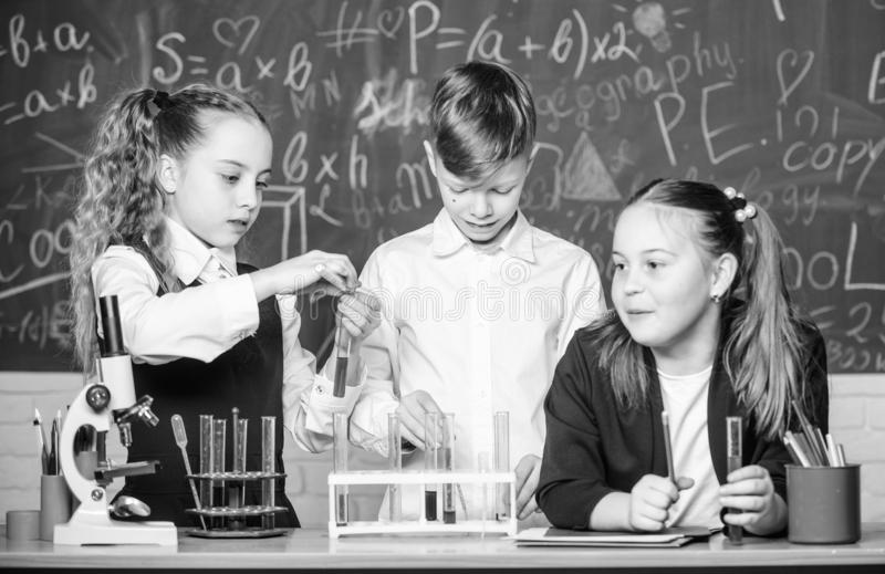 Пробирки с веществами Официальное образование Девушки и эксперимент по школы проведения студента мальчика с жидкостями E стоковое изображение