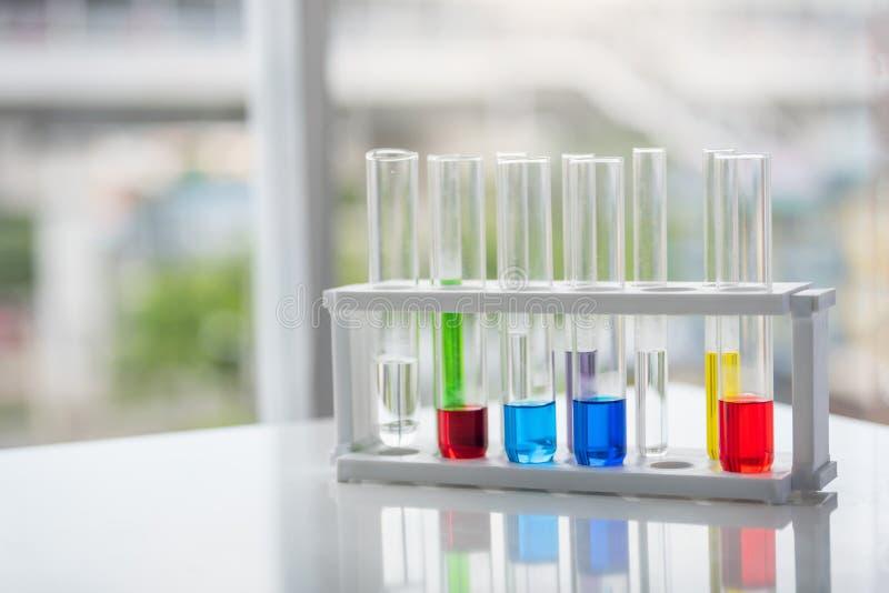 Пробирки с красочным химикатом на таблице Химия co науки стоковые изображения