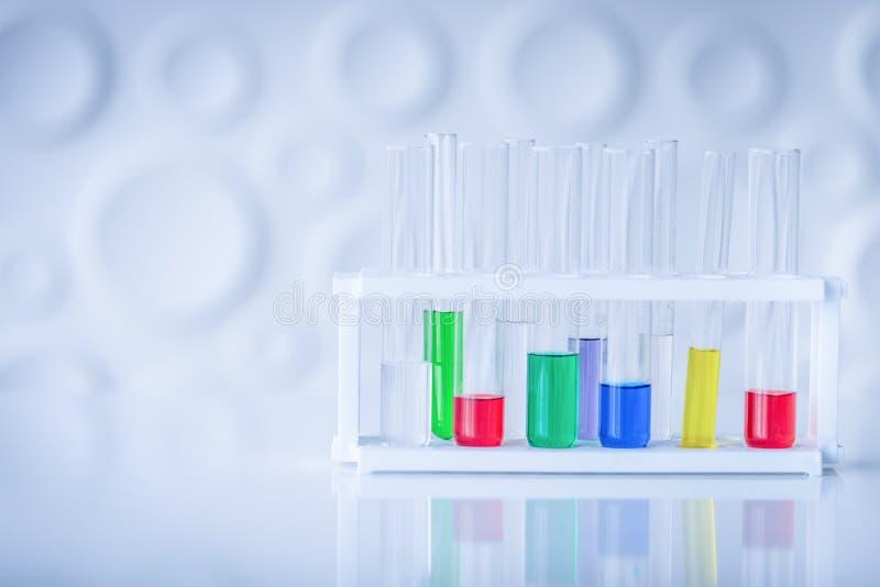 Пробирки с красочным химикатом на таблице Химия co науки стоковое фото