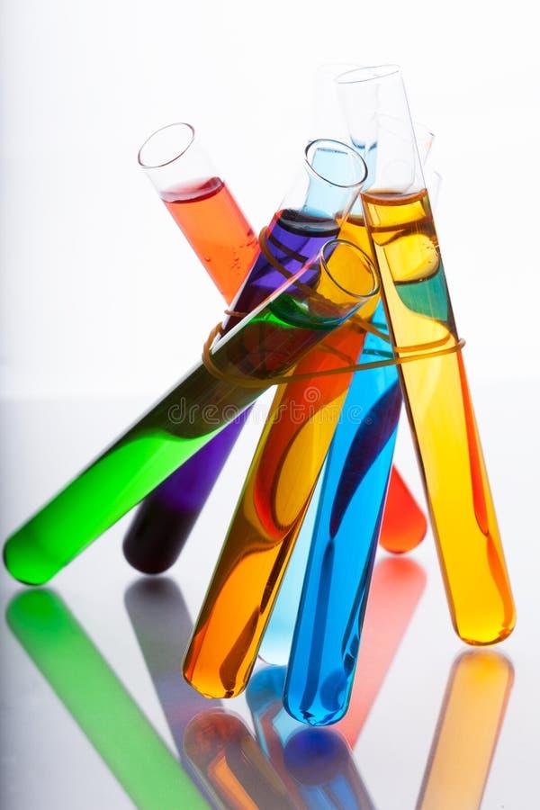 Пробирки с покрашенной жидкостью в цветах спектра на белизне стоковое фото rf