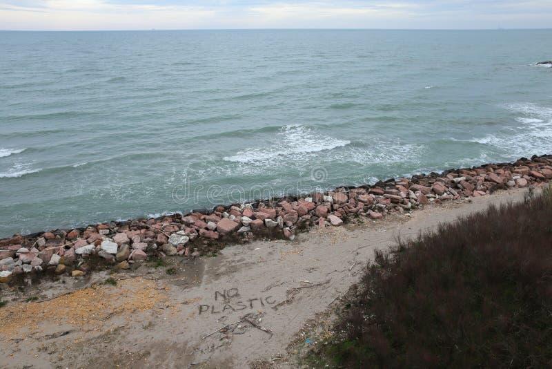 Проблема окружающей среды : Пластмасса на пляже с сочинительством sos Разлитый отброс на пляже стоковые изображения rf
