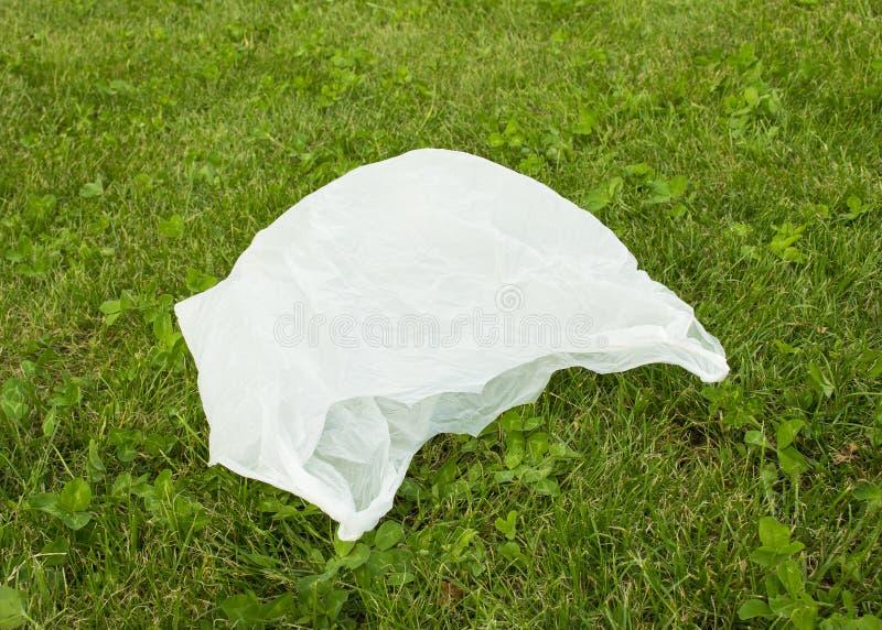 Проблема с загрязнением Пакет лежит на зеленой траве Хлам на лужайке стоковые фото