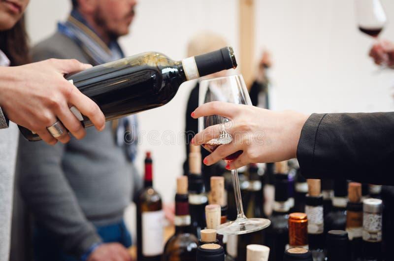 Пробовать опыт с женским сомелье служа стекло вина Barolo красного стоковое фото rf