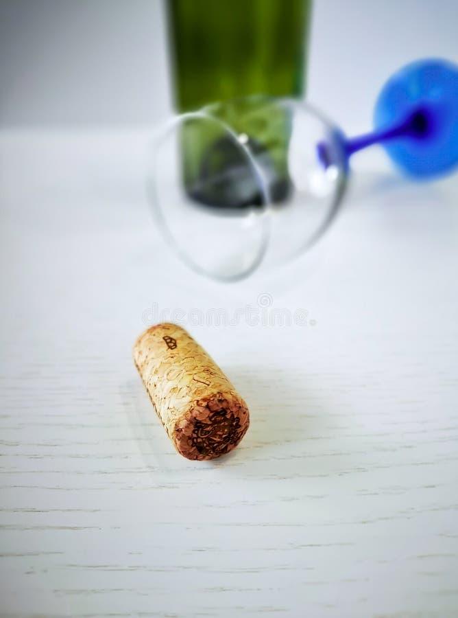 Пробочка вина лежит на белом деревянном столе На заднем плане, переворачиванное стекло с голубой ногой и пустая бутылка вина стоковые изображения