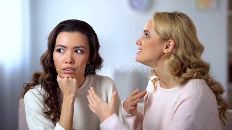 Пробуренная азиатская женщина слушая ее надоедливый друг, невовлеченный в разговоре стоковое изображение