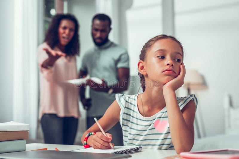 Пробуренная девушка изучая пока ее родители обсуждая ее плохих преподавателей стоковое изображение rf