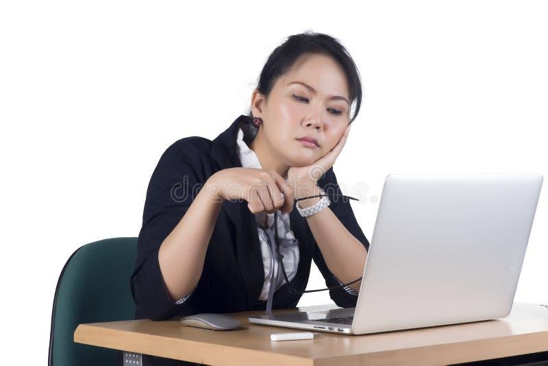 Пробуренная женщина дела работая на компьтер-книжке смотря очень сверлильна на th стоковое изображение