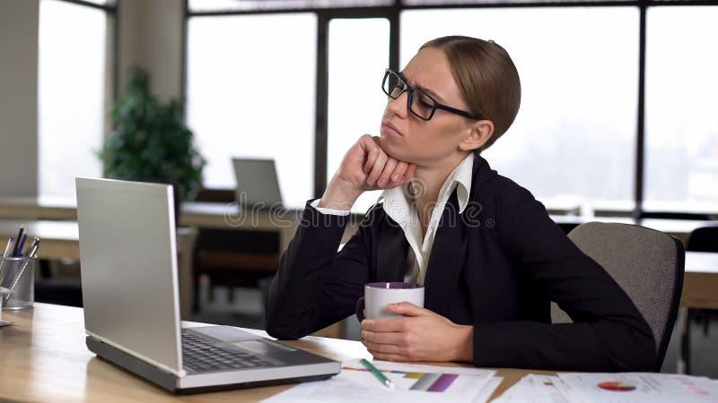 Пробуренная женщина имея перерыв на чашку кофе в офисе, неудовлетворенном с работой, недостаток идей стоковые изображения