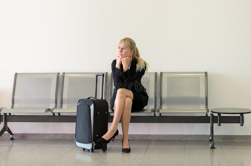 Пробуренная коммерсантка ждать полет стоковая фотография